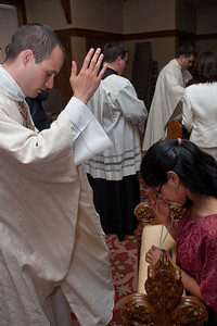 Father Llane Briese blesses Silvia, a 14-year old student from St. John Neumann School. (Photo by Thomas Spink)