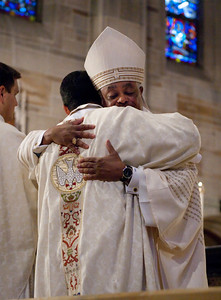 Archbishop Wilton D. Gregory, facing camera, hugs newly ordained Father Mario Lopez during the presbyteral greeting of peace. (Photo by Thomas Spink)