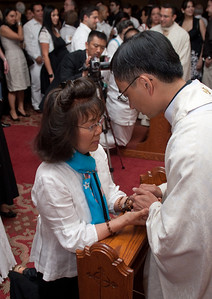 A member of the faithful receives a blessing from Thang Pham (right) at the reception. (Photo by Thomas Spink)