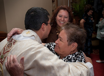 Father Mario Anibal Lopez-Castro (left) gets a hug from Rosa Betancourt (center) and Concepcion Phillips (formerly from Columbia) from St. Vincent de Paul Church in Dallas, Georgia after receiving a blessing at the reception. (Photo by Thomas Spink)