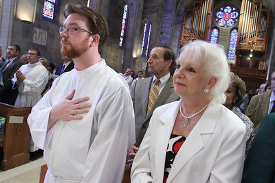 Ordination candidate Dennis Dorner Jr., foreground left, stands with his mother Susan, as Michael Revak, background left, stands among his relatives and friends during the reading of Matthew's Gospel.