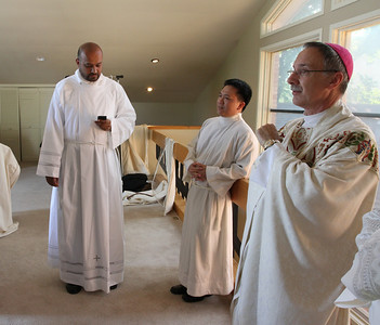 Minutes before the May 26 transitional diaconate ordination, Gaurav Shroff, left, makes one final post to Facebook as Cong Nguyen, center, relaxes in the company of Bishop Luis Zarama, auxiliary bishop of Atlanta, and the other four ordination candidates.