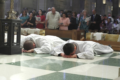 Michael Revak, left, and Feiser Munoz Polanco prostrate themselves before the altar during the Litany of Saints at the Cathedral of Christ the King, Atlanta.
