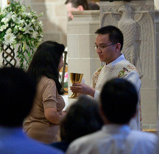5-28-2011 - Atlanta, Georgia - Tri John-Bosco Nguyen (right) gives the cup of precious blood to communicants during the liturgy of the Eucharist. The Rite of Ordination to the Order of Diaconate was celebrated at the Cathedral of Christ the King in Buckhead Saturday, May 28, 2011 for Mark Richard Starr and Tri John-Bosco Nguyen. Archbishop Wilton D. Gregory was the main celebrant and homilist. (Photo by Thomas Spink)