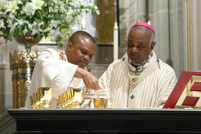 Archbishop Wilton D. Gregory, right, looks on as newly ordained transitional deacon, Charles Okeke, pours wine into the chalices during preparation of the altar for Liturgy of the Eucharist.