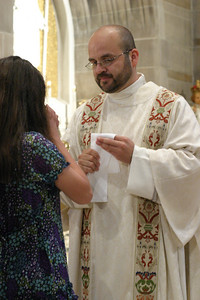 Transitional deacon Juan Jose Sanchez offers the Communion cup to a woman attending the May 29 diaconate ordination at the Cathedral of Christ the King, Atlanta.