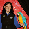 Wild Life Live Animal keeper Shannon poses with Pele the Macaw in front of the backdrop he painted for the event.