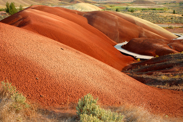 """""""I want to go back"""" - Ice Age by Pete Yorn  Another """"otherworldly"""" group of Painted Hills. The Kool-aid cherry red of these hills can really wake you up first thing in the morning. We spent a half hour walking around the path admiring the beauty of this 30 million year old mound of color and clay. If there's one place to visit in Oregon, I'm convinced this is the place to see."""