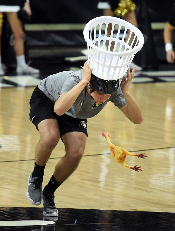 . A student from the audience tries to catch rubber chickens for a prize. For more photos of the game, go to Buffzone.com.  Cliff Grassmick / Staff Photographer/ January 26, 2018