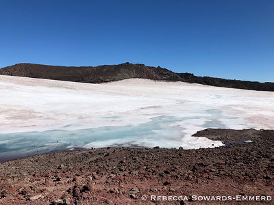 After climbing up that steep red slog, you pop out on the rim of the summit crater. But if you want to tag the summit proper you have to walk all the way over to the other side! The crater is filled with snow, but at this time of year a lot was melting out so no one was walking on it.