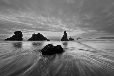 Seastacks with tidal surf streaking across sandy beaches, Bandon, Oregon