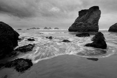 Seastacks with tidal surf streaking across sandy beaches, Bandon, Oregon