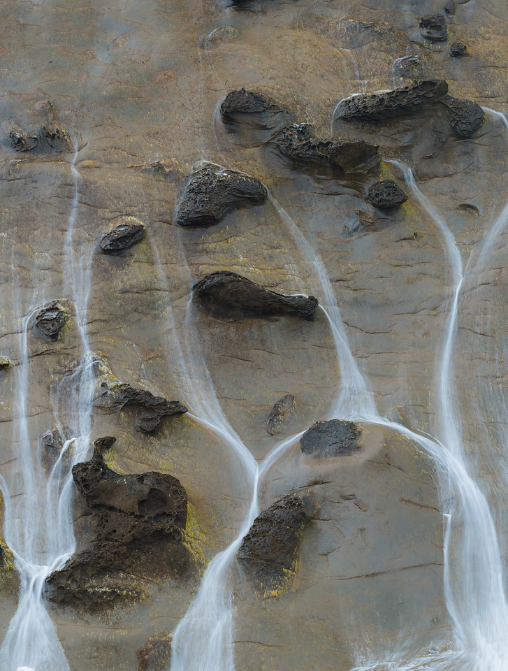 Shore Acres State Park with sandstone bluffs being pounded by tidal shifting surf, creating waterfalls over concretions in the stone.  Oregon