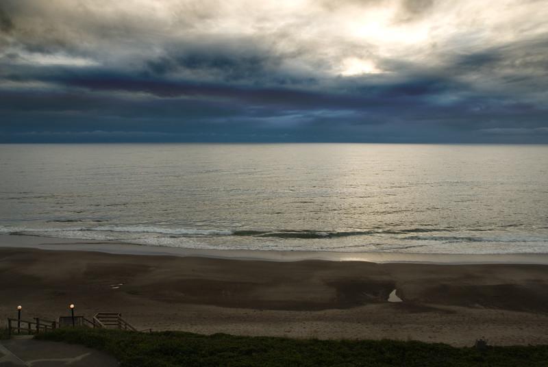 The sun peeking through the clouds, setting on the beautiful Oregon Coast viewed from the Cavalier.<br /> D200_2007-07-17DSC_2332-SunsetCloudy-nice-2 copy.jpg
