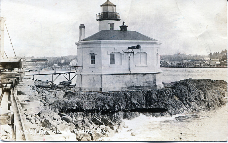 A 20th century postcard view of the Coquille River Lighthouse showing the foghorn and the elevated wooden walkway leading to the structure.