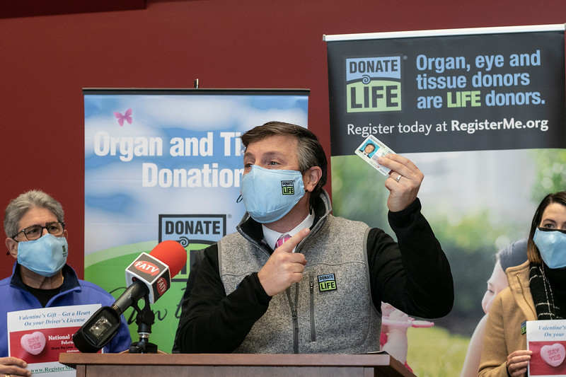 "The City of Fitchburg celebrated Valentine's week by joining an organ donor recipient and others touched by organ donation to celebrate national Organ Donor Day and ask people to ""Have a Heart and get a Heart"" by registering as a donor at the RMV when getting or renewing your driver's license, Real ID, or ID. Holding up his his license is Matt Boger with New England Donor Services to show of where you would put the heart when you register at the RMV to be a donor. SENTINEL & ENTERPRISE/JOHN LOVE"