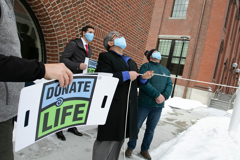 """The City of Fitchburg celebrated Valentine's week by joining an organ donor recipient and others touched by organ donation to celebrate national Organ Donor Day and ask people to """"Have a Heart and get a Heart"""" by registering as a donor at the RMV when getting or renewing your driver's license, Real ID, or ID. Dan Murphy, in green jacket, a double lung recipient helps Mayor Stephen DiNatale raise an organ donor flag at the end of the press conference. SENTINEL & ENTERPRISE/JOHN LOVE"""