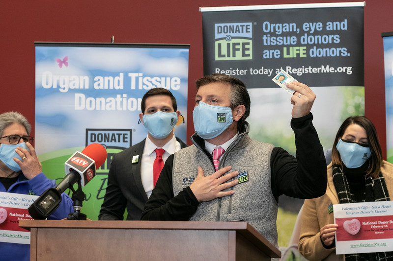 """The City of Fitchburg celebrated Valentine's week by joining an organ donor recipient and others touched by organ donation to celebrate national Organ Donor Day and ask people to """"Have a Heart and get a Heart"""" by registering as a donor at the RMV when getting or renewing your driver's license, Real ID, or ID. Holding up his his license is Matt Boger with New England Donor Services to show of where you would put the heart when you register at the RMV to be a donor. SENTINEL & ENTERPRISE/JOHN LOVE"""