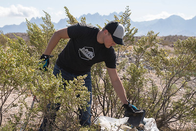 Tyler, with Organ Mountain Outfitters, cleans up trash outside of Las Cruces, New Mexico.