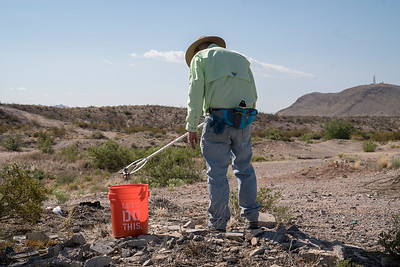 Michael Mckey, with the Friends of the Organ Mountains-Desert Peaks, cleans up trash outside of Las Cruces, New Mexico.