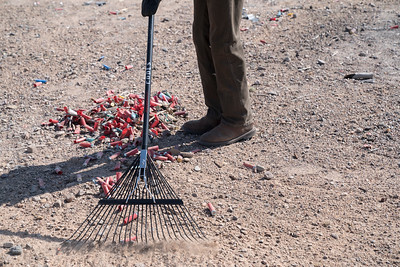 Rico Smith, from the Bureau of Land Management, rakes up shot gun shells at the Friends of Organ Mountains-Desert Peaks and the Illegal Dumping Partnership clean up in Las Cruces, New Mexico.