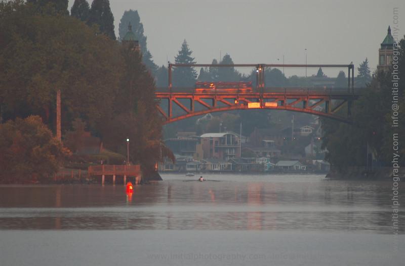 Sunrise glow off of the Montlake Bridge with rower under bridge