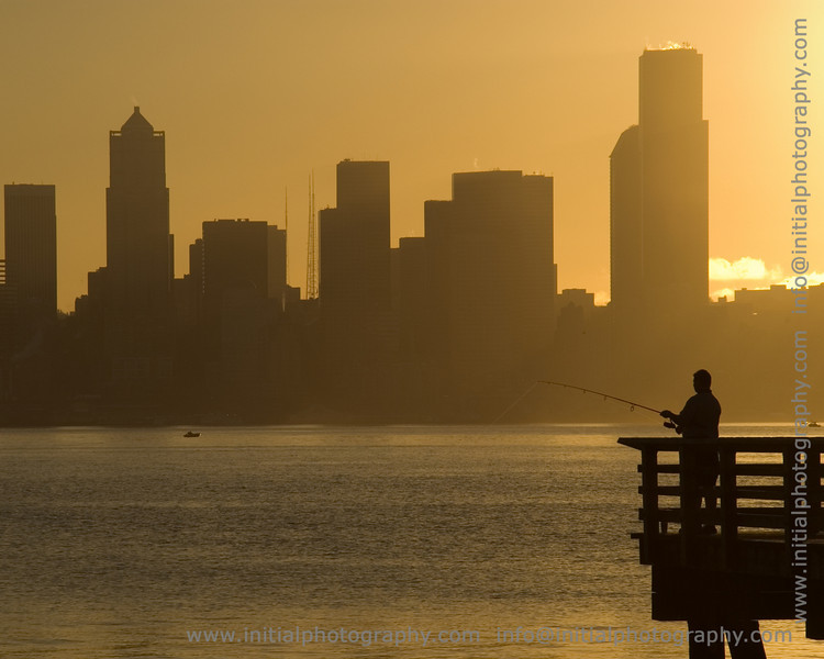 man fishing off a pier at Alki with downtown Seattle in the background