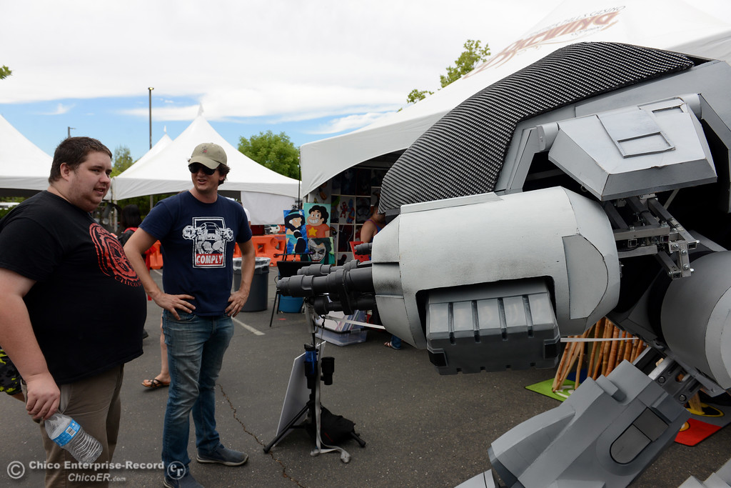 """. Gabriel Regan, of Chico, left, takes a look at ED-209, the robot from the \""""Robocop\"""" movie with one of its creators, David Codeglia, of Ghostlight.com during Oro Con on Saturday, June 3, 2017, at Feather Falls Casino in Oroville, California. (Dan Reidel -- Enterprise-Record)"""