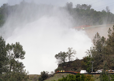 Little worker next to the massive spray of the spillway March 27, 2017 in Oroville, California. (Emily Bertolino -- Enterprise-Record)