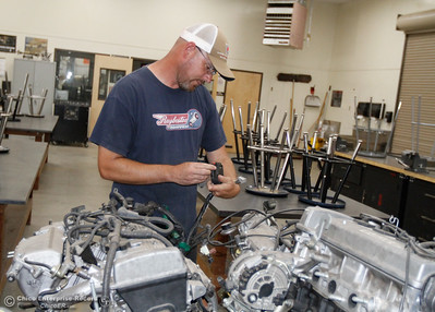 Automotive technology teacher Daniel Briggs looks down at a motor as he prepares his classroom for the start of the fall semester August 15, 2016 at Oroville High School in Oroville, Calif. (Emily Bertolino -- Mercury Register)