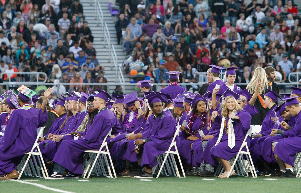 . Students in the Oroville High School class of 2017 wave to their friends and family as they enter the commencement ceremony Thursday June 8, 2017 at Harrison Stadium in Oroville, California. (Emily Bertolino -- Enterprise-Record)