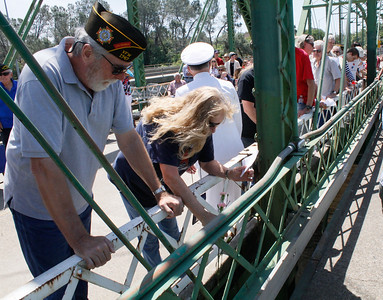 Alan and Jeri Wixom, left to right, toss flowers into the Feather River to honor all veterans during a Memorial Day ceremony Monday May 29, 2017 on the green bridge in downtown Oroville, California. (Emily Bertolino - Mercury Register)