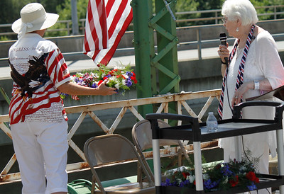 Jeri Wixom, left, throws a wreath into the Feather River to honor and remember veterans who have lost their lives as Sherry Morehouse looks on during the annual Memorial Day ceremony Monday May 29, 2017 on the green bridge in downtown Oroville, California. (Emily Bertolino - Mercury Register)
