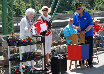Sherry Morehouse conducts the tolling of the bell as Bob Morehouse rings the bell to honor and remember lives lost during the annual Memorial Day ceremony Monday May 29, 2017 on the green bridge in downtown Oroville, California. (Emily Bertolino - Mercury Register)