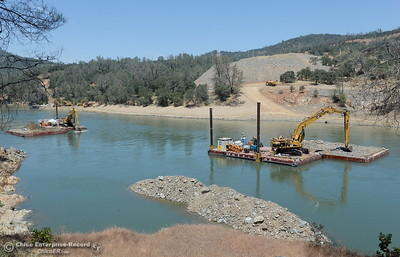 Excavators work on a barge downstream as construction continues near the Lake Oroville Dam Spillway Wednesday May 24, 2017.  (Bill Husa -- Enterprise-Record)