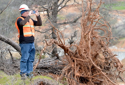 A man takes a photo with a cell phone as work continues to remove debris from below the Oroville Dam spillway Monday March 6, 2017.  (Bill Husa -- Enterprise-Record)