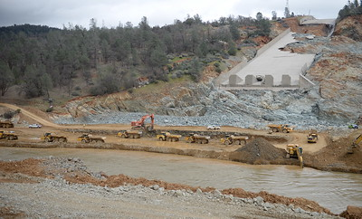 Many dumptrucks are seen as work continues to remove debris from below the Oroville Dam spillway Monday March 6, 2017.  (Bill Husa -- Enterprise-Record)