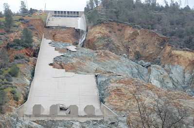 Although reports show a zero cfs outflow at the spillway, water, presumably leaking from the flow control system is seen flowing down one side as work continues to remove debris from below the Oroville Dam spillway Monday March 6, 2017.  (Bill Husa -- Enterprise-Record)