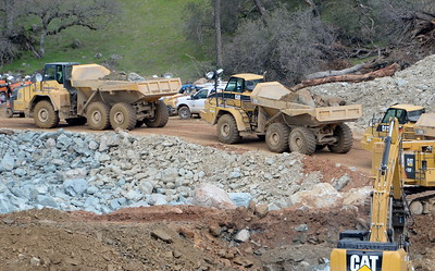 Dump trucks and excavators are seen as work continues to remove debris from below the Oroville Dam spillway Monday March 6, 2017.  (Bill Husa -- Enterprise-Record)