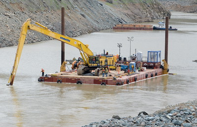 A large excavator with a long reach works from a barge to dig the outflow area deeper as work continues to remove debris from below the Oroville Dam spillway Monday March 6, 2017.  (Bill Husa -- Enterprise-Record)