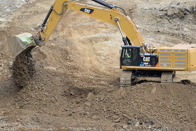 An excavator with a large bucket piles up rocks and mud as work continues to remove debris from below the Oroville Dam spillway Monday March 6, 2017.  (Bill Husa -- Enterprise-Record)
