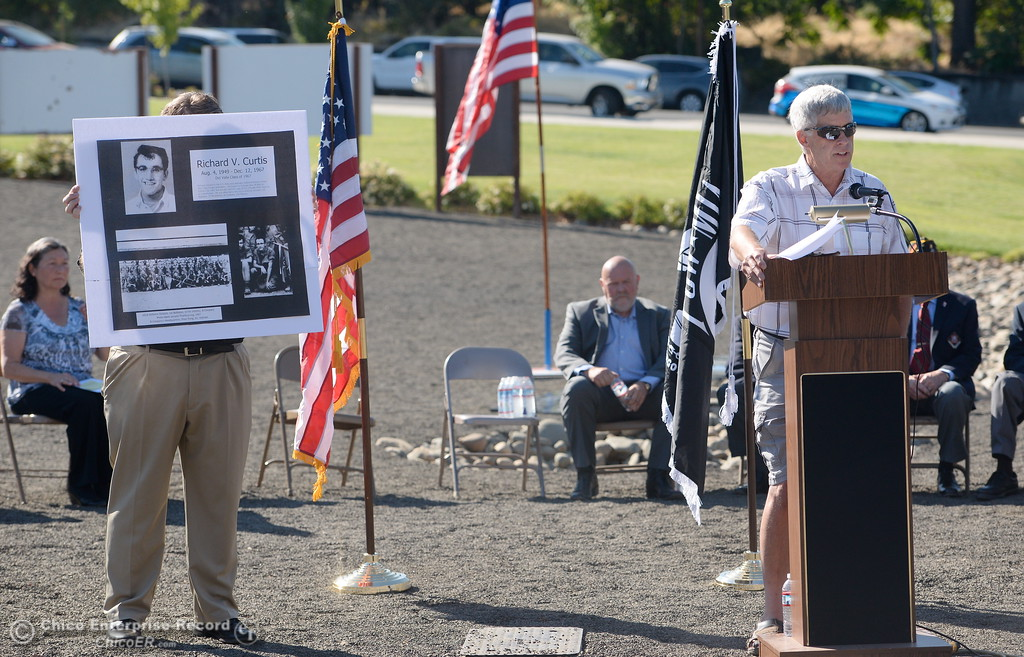 . A portrait of Veteran Richard V. Curtis is shown as Don Noble tells his story during the Oroville Veterans Memorial Park opening ceremony Friday July 28, 2017. (Bill Husa -- Enterprise-Record)