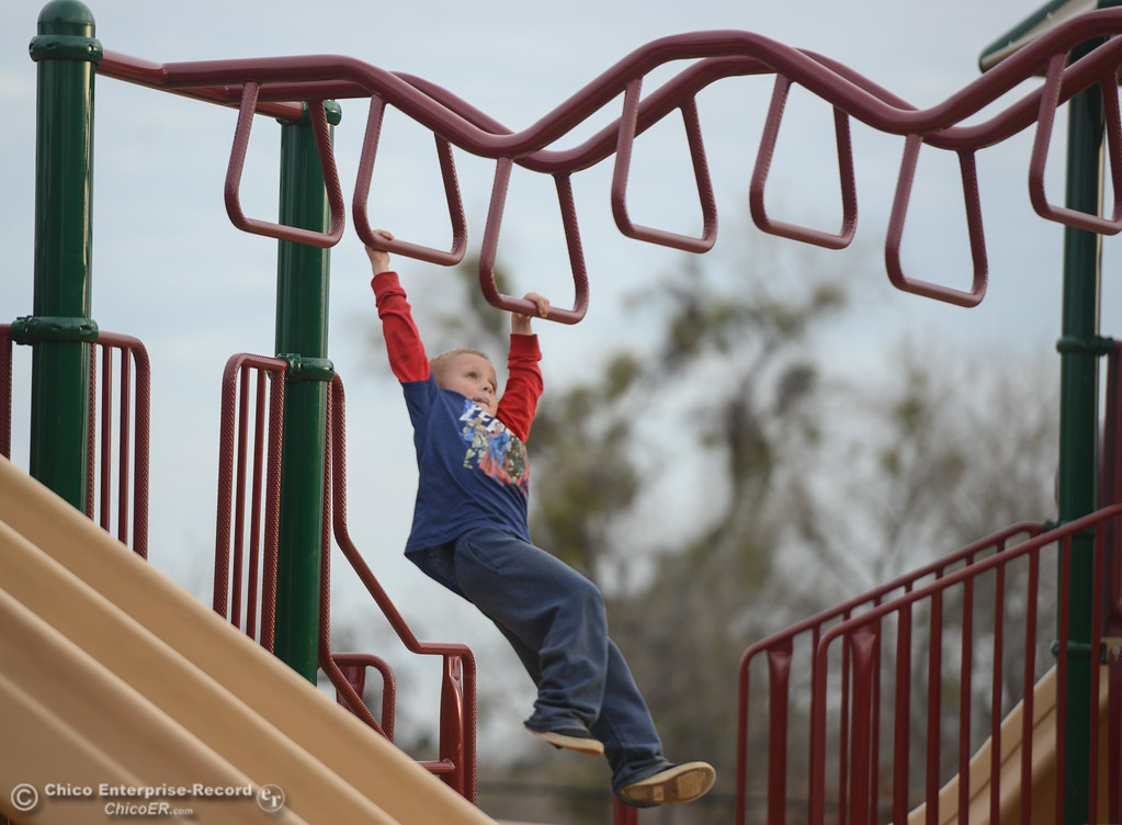 . Kaleb Fox, 6, makes his way across the monkey bars Tuesday January 16, 2018 at Riverbend Park in Oroville, California. (Emily Bertolino -- Enterprise-Record)