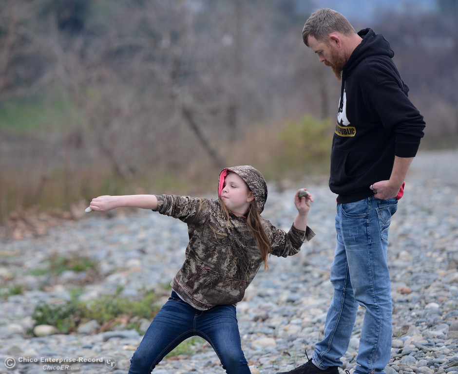 . Patience, 9, and Bill Cross practice skipping rocks Tuesday January 16, 2018 at Riverbend Park in Oroville, California. (Emily Bertolino -- Enterprise-Record)