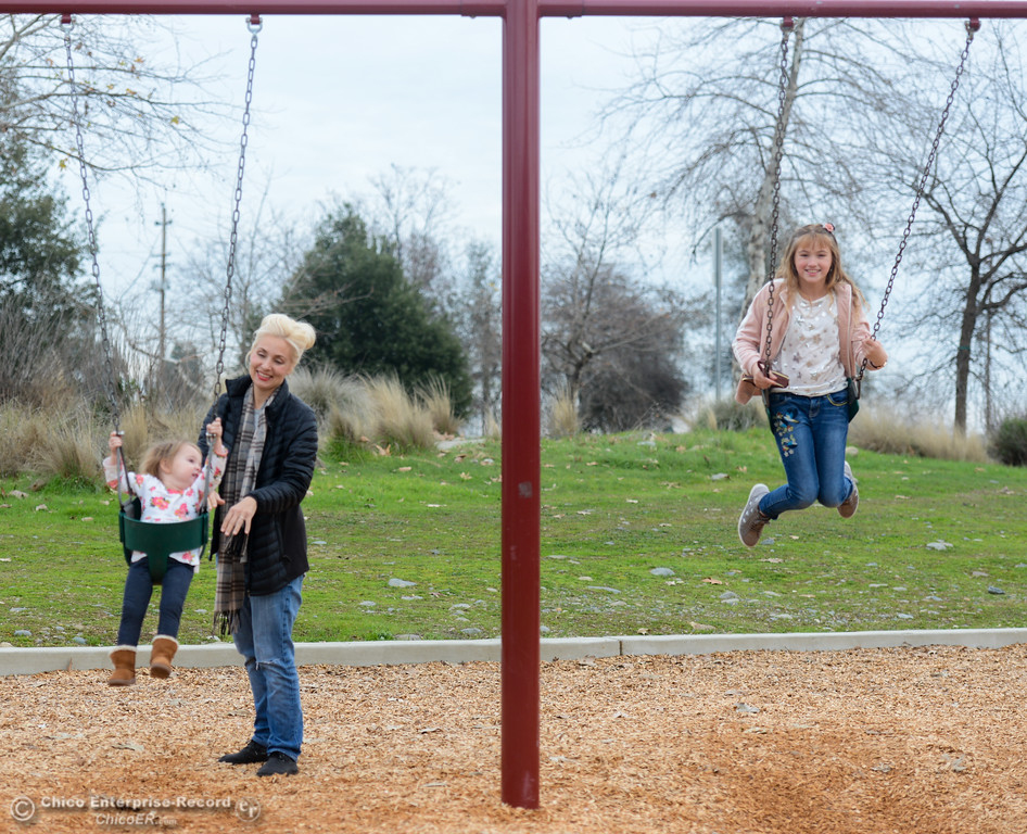 . Jenae King Romaguera pushes her daughter Genevieve, 22 months, on the swing as Eleanor King Romaguera, 11, swings along Tuesday January 16, 2018 at Riverbend Park in Oroville, California. (Emily Bertolino -- Enterprise-Record)
