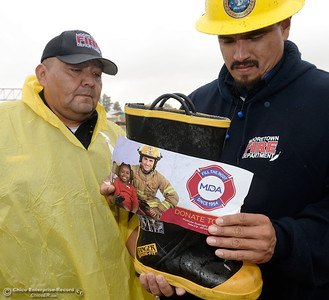 Firefighter Gilbert Rodriguez tries to apply a new sticker to a boot as he and Engineer Gordon Garcia, left along with other Mooretown Rancheria Fire representatives brave the rain on the corner of Feather River Blvd. and Oro Dam Blvd. to Fill the Boot for MDA in Oroville, Calif. Friday Oct. 14, 2016. (Bill Husa -- Enterprise-Record)