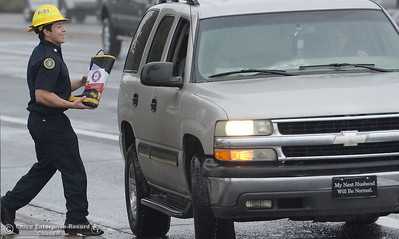 Mooretown Rancheria Firefighter Martin Carrillo smiles as he braves the rain on the corner of Feather River Blvd. and Oro Dam Blvd. to Fill the Boot for MDA in Oroville, Calif. Friday Oct. 14, 2016. (Bill Husa -- Enterprise-Record)