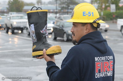 Firefighter Gilbert Rodriguez holds a boot as he and other Mooretown Rancheria Fire representatives brave the rain on the corner of Feather River Blvd. and Oro Dam Blvd. to Fill the Boot for MDA in Oroville, Calif. Friday Oct. 14, 2016. (Bill Husa -- Enterprise-Record)
