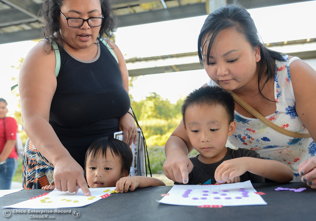 . Titus Thao, 3, and Gavyn Thao, 5, with help from Jamie Her and Kathy Her (counter clockwise) solve a computer programming problem on paper during the Explorers Faire  Wednesday September 27, 2017 at Butte College in Butte Valley, California. (Emily Bertolino -- Enterprise-Record)