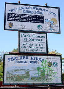 A sign says the park closes at sunset and vehicles in lot may be locked in while another lower sign has been vandalized at Riverbend Park in Oroville, Calif. Friday Sept. 22, 2017. (Bill Husa -- Enterprise-Record)